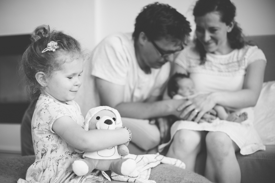 Uvolněný rodinný portrét. Během newborn focení si starší sourozenec hraje s medvídkem a balí ho do zavinovačky jako miminko